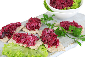 Beet salad on toasts and in plates on board isolated on white