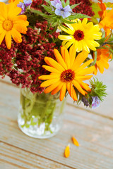 Bouquet of autumn flowers in vase on wooden background