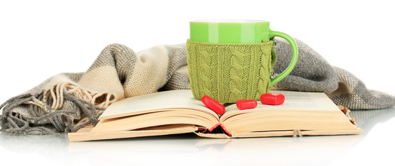 Cup with knitted thing on it and open book isolated on white
