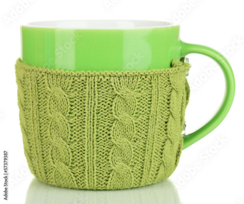 Cup with knitted thing on it isolated on white