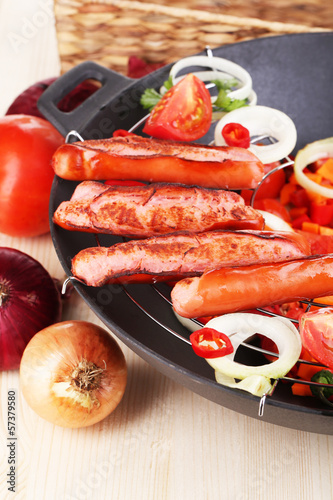 Delicious sausages with vegetables in wok