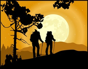 Two climbers in silhouette climbing the mountain