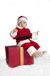 little santa claus seated on a christmas present i