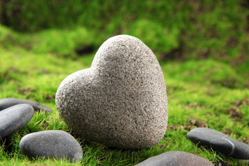 Grey stone in shape of heart, on grass background