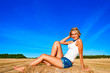 Beautiful woman in jeans short  posing on a wheat bale