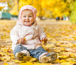 little girl among autumn leaves