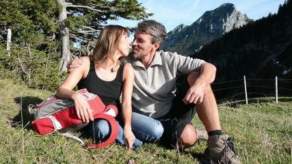 Paar küsst sich beim Wandern auf der Wiese im Gebirge