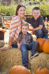Portrait of Attractive Mother and Her Sons at Pumpkin Patch.