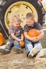 Two Boys Holding Pumpkins Talking and Sitting Against Tractor Ti