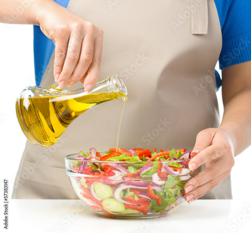 Cook is pouring olive oil into salad - 57383147