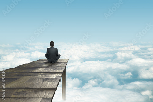 businessman sitting on pier