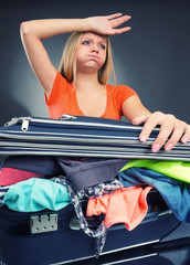 Exhausted young woman packing luggage