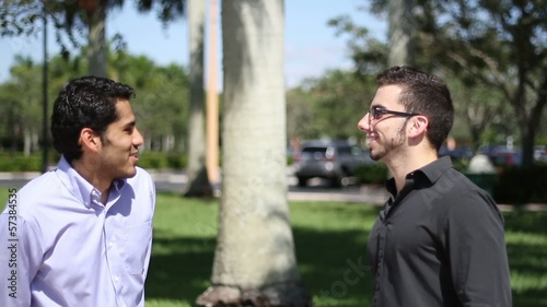 Two businessmen chat outdoors. colleagues friendly discussion