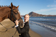 Portrait of a teenage girl with a favorite horse at the sea.