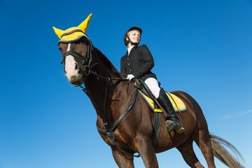 Teenage girl sitting on a horse