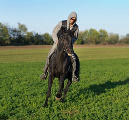 Man riding black horce on field