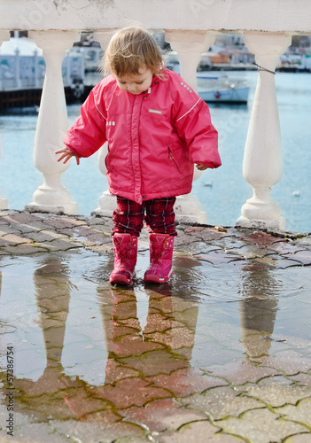 baby girl walking in puddle