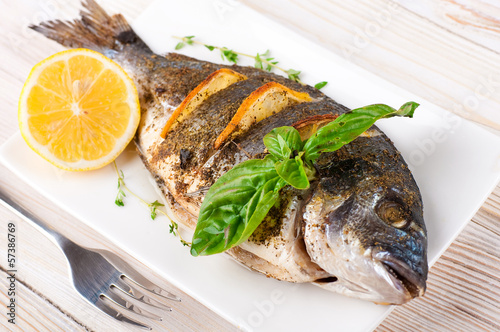 canvas print picture Dorado fish with lemon and spices on a wooden board
