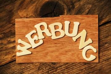 das Wort WERBUNG auf Holztafel