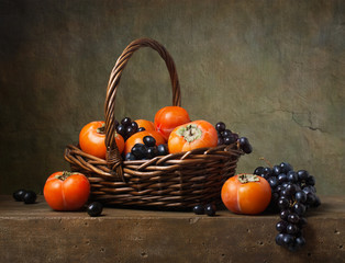 Still life with persimmons and grapes in a basket