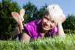 Blonde Smiling woman laying on a grass field