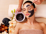 Cosmetologist smears cosmetic mask on the face of  woman poster