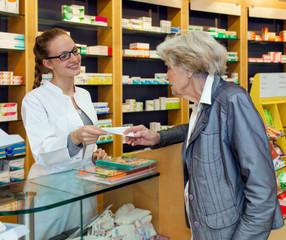 Pharmacist serving a senior lady.