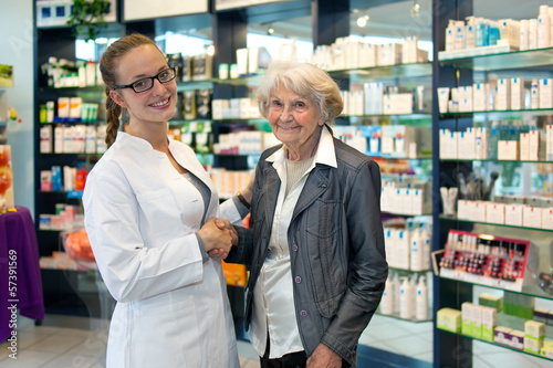 Senior lady shaking hands with a pharmacist.