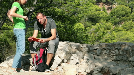 Lost couple on hiking trip looking at map on tablet computer