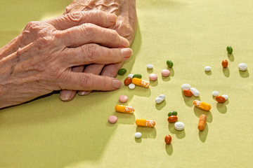 Hands of an elderly lady with medication.