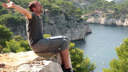 Man with laptop relaxing on cliff in beautiful nature scenery
