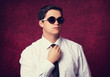 Elegan man in sunglasses at red background.