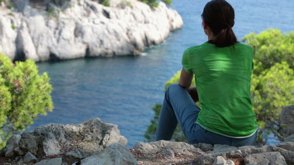 Woman sitting, relaxing in beautiful nature scenery