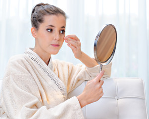 Beautiful woman in bathrobe looks at the mirror