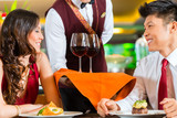 Waiter serving Chinese couple wine in fancy restaurant