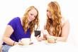 junge frauen beim kaffee schauen auf ihr smartphone