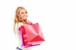 glückliche junge frau mit einkaufstüten schaut über die schul