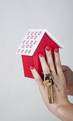 Hands and keys and a model house