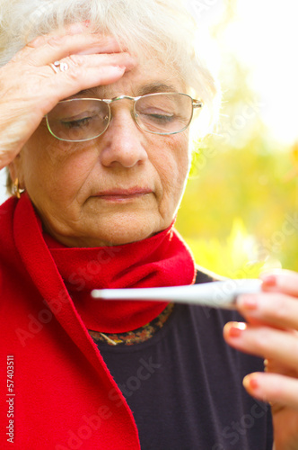 Old woman taking her temperature