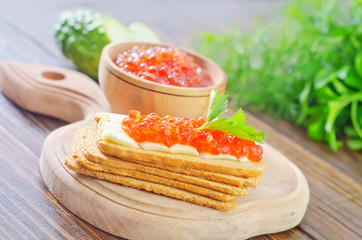toasts with red caviar on board