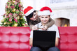 Asian couple in christmas hats shopping online