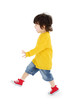Little boy in yellow shirt walks isolated on white