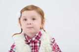 Little girl in fur vest grimaces and looks away on white