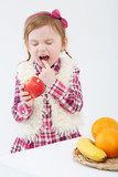 Little girl with apples bits her tongue near table with fruits