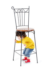 Little boy hides under high wrought-iron chair isolated