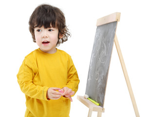 Little boy with chalk stands near chalkboard isolated