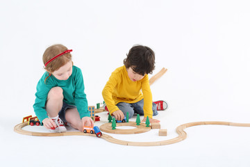 Little cute girl and boy roll trains on wooden railway