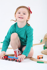 Little smiling girl plays with train and wooden railway