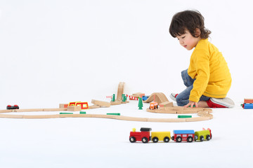 Little boy play with toy trains and big wooden railway