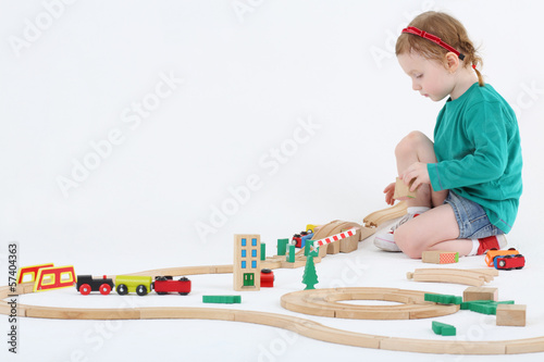 Little pretty girl builds railway from wooden parts  on floor